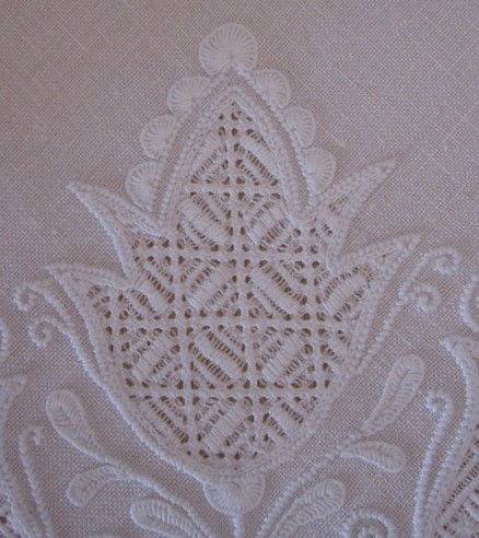 Tulip embellishment with half-eyelet scallops of differing sizes. The thread weight and the density of the stitches are both correct.