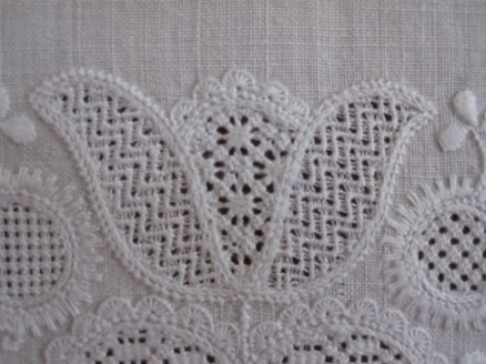 Tulip embellishment with uniform half-eyelet scallops. The thread weight and the density of the stitches are both correct.