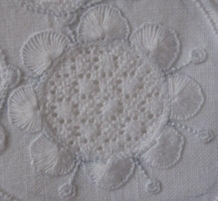 Circle outlined with uniform and evenly distributed half-eyelet scallops. However, they are too large. The thread weight and the density of the stitches are both correct. A larger scallop needs more stitches to become sufficiently covered; it is difficult to get an orderly appearance with so many stitches radiating from the same point.