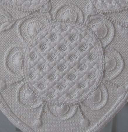 Circle outlined with uniform and evenly distributed half-eyelet scallops. The individual scallops are divided and worked with the appropriate thread weight, and the stitches have been worked with the appropriate density. The additional embroidered parts also utilize the correct thread weight.