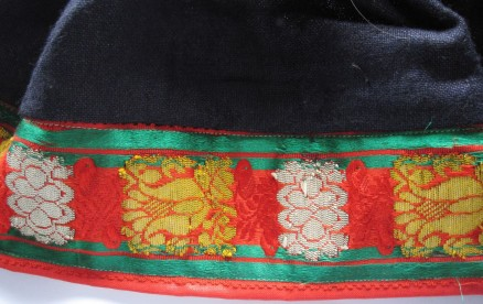 "Skirt of the red costume, trimmed with red ""Damest"" and additionally decorated with a 6 cm wide extra fancy silk ribbon."