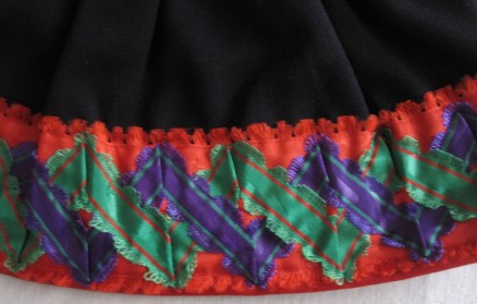 "Skirt of the red costume, trimmed with red ""Damest"" and additionally decorated with an 8 cm wide red silk damask ribbon onto which two silk ribbons were sewn creating a double zig-zag line."