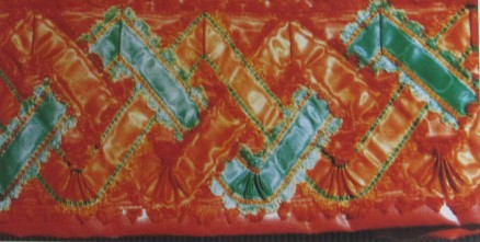 "Skirt of the red costume, trimmed with red ""Damest"" and additionally decorated with an 8 cm wide silk ribbon onto which three silk ribbons were sewn creating a triple zig-zag line."