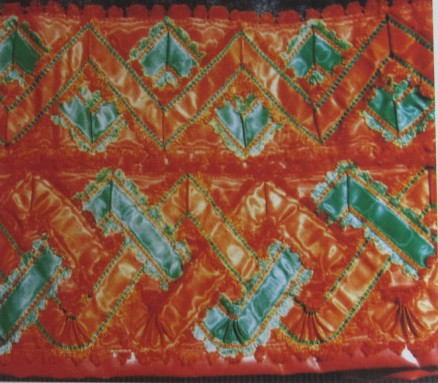 "Skirt of the red costume, trimmed with red ""Damest"" and additionally decorated with an 8 cm wide silk ribbon onto which three silk ribbons were sewn creating a triple zig-zag line and additionally decorated with a 6 cm wide silk ribbon onto which two silk ribbons were sewn creating a double zig-zag line."