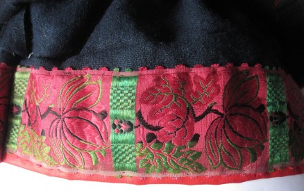 "Skirt of the red costume, trimmed with red ""Damest"" and additionally decorated with a 8 cm wide silk ribbon."