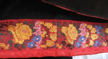 "Skirt of the red costume, trimmed with red ""Damest"" and additionally decorated with a 4 cm wide silk ribbon."