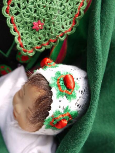 baby boy's christening cap decorated with tritzers and berries stuffed with a bean; image from the booklet Die Schwälmer Tracht von der Wiege bis zur Bahre by Erika Decker
