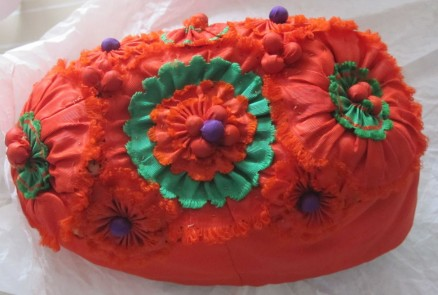 tritzer embellishment, with tucked berries stuffed with peas, on a cap for a little girl