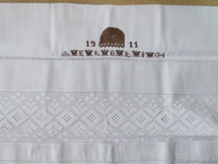 Parade cushion decorated with machine-made lace, Peahole hem and Four-Sided stitch hem, and a crown with the year and initials in Cross stitch.